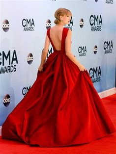 Taylor wisely allows her gown's open back and full skirt to take center stage by pinning up her be-banged blond locks. Is her scarlet dress just as dramatic from behind? Vote, then let's take a peek at what's happening above her neck …