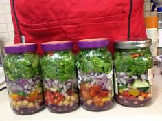 Salads made for the work week. Dressing on bottom, garbanzo beans, sweet mini peppers, red onion, diced cucumber and lettuce on top. Stored upright in mason jars should last 5 days.