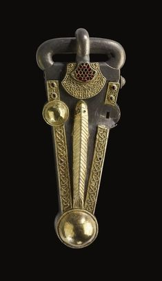 Silver buckle with a cast oval loop and shield-on-tongue covered by a sheet gold plate, edged with beaded wire, and divided into two crescentic panels flanking a central rectangle, all filled with collared granules.       Early Anglo-Saxon 7thC(mid). | © Trustees of the British Museum