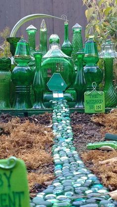 Thrift store bought green glass bottles to make a mini Emerald City .. loving this