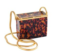 CHANEL Tortoise Lucite mini evening bag in tortoise with extra long snake chain and CC logo at top.