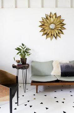 Love this contemporary meets midcentury mixed style living room with triangle floor decals, midcentury slatted wood bench with cushions, faux sheepskin and velvet throw pillows draped on top, raw wood hairpin leg side table and gorgeous traditional gold petal sunburst mirror on the wall.