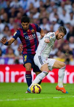 Luis Suarez of Barcelona and Sergio Ramos of Real Madrid CF battle for the ball during the La Liga match between Real Madrid CF and FC Barcelona at Estadio Santiago Bernabeu on October 25, 2014 in Madrid, Spain.