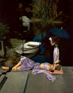 ca. 1948 --- Model in purple skirt and bandeau top, on pink cushion with model standing above holding umbrella, both women are in front of small rowboat. vintage everyday: Extraordinary Color Fashion Photography Taken During the 1940s by John Rawlings