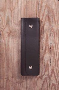 Gediget penfodral i läder från tyska Bindewerk. Fodralet öppnas med tryckknappar. På insidan finns det plats för 5 stycken pennor som hålls fast med elastiska band. Läder blir bara finare med tiden vilket gör att ditt penfodral kommer att få en personlig och högst unik karaktär.