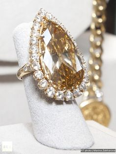 The Burton Cognac-Colored Diamond ring for Elizabeth Taylor (1974) by Van Cleef & Arpels Ring set with a modified pear-shaped fancy deep brownish-orange yellow diamond, weighing approximately 32.14 carats, within a circular-cut diamond surround, the shoulders decorated with circular-cut diamonds, mounted in gold-topped platinum.