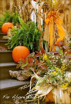 Autumn decor. Corn stalks lining the stairs, ferns, pumpkins and corn husks in the flower pot. Very nice.