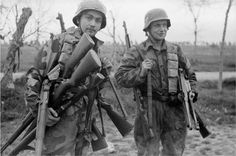 German soldiers with lots of captured american equipment, all Garands, Thompsons and ammunition belts, notice how one of said Thompsons is a pre-war M1928, a nice comparison with the M1A1 alongside it.
