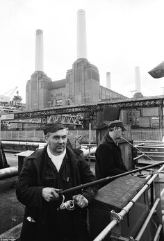 Two workers in 1981 fish from a wharf on the River Thames just in front of the towers of the power station