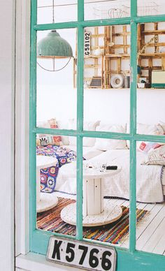 Love the aqua window, mirrored in the lamp, and the pops of colour in the room. Hate the shabby tables, but love the repurposing idea
