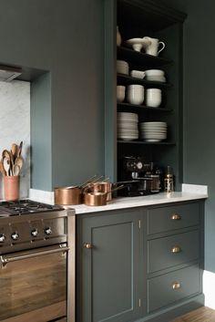 Cuisine raffinée en vert foncé. Mets en valeur les matières nobles et chic comme la porcelaine blanche, le cuivre, le laiton, la poterie ou le marbre