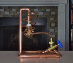 This Steampunk-Style lamp is made from copper pipes and fittings. The Lamp is lit by turning the faucet dial thereby keeping the aesthetics of