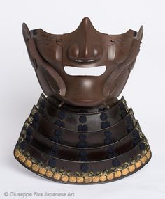 "Ryubu menpo, Myochin school. Mid Edo period (1615-1867). A samurai armor mask of me-no-shita-men type with ""noble"" expression (ryubu). The nose is detatchable and two yadome run along the cheeks to reinforce the mask and to hold the kabuto's laces firmly. The type and the features suggest a smith from the Myochin school. -Giuseppe Piva Arte Giapponese-"