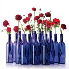 FLOWER SHOW Deck your tables with fresh red flowers displayed in blue glass bottles. You can stick to one type or mix a variety of buds (ranunculus, anemones, and Gerber daisies, for example). Just keep the palette consistently rosy. Arrange the bottles in clusters, or line them down the center of the table.  (Blue wine bottles, Home Brew It, $13/12; homebrewit.com.)