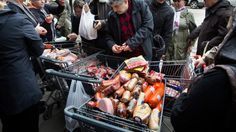 A customer browses food piled into shopping carts on Brighton Beach Avenue, Wednesday, Oct. 31, 2012, in the Brooklyn borough of New York.