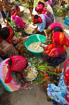 Kuna Indian women wearing native costumes with Mola embroideries cutting up bananas, San Blas Islands, Panama