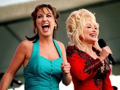 Lee Ann Womack, left, is surprised when Dolly Parton joins her on stage while Womack is singing a Parton song at Fan Fair at the Tennessee State Fairgrounds.