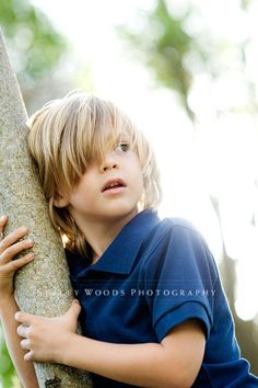 boy hugging tree holding post long hair confused scared