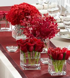 "The FTD® Modern Grace™ Centerpiece consists of five individual bouquets to create one exceptional look. Clear glass cube vases in varying heights each carry a bouquet of one of the following flowers, including red roses, bi-colored red and white roses, red tulips, red mokara orchids, and red carnations to give your head table a look of elegant distinction. Approximately 5-10""H x 3-10""W."