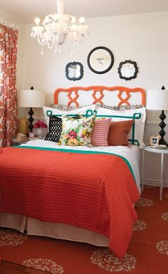 A colourful bedding set, drapes and a shapely white chandelier and bedside lamp make a bold decorating statement. Glossy orange paint makes this vintage headboard pop, punctuating the graphic nature of its design.