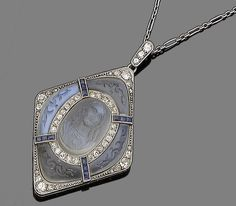 A moonstone, sapphire and diamond pendant necklace, circa 1915  The lozenge-shaped plaque, centrally-set with an oval-shaped moonstone cameo carved to depict Christ, within a single-cut diamond border, to a further surround of foliate carved moonstones, highlighted with calibré-cut sapphires, old brilliant, single and rose-cut diamonds, to a fetter-link chain, diamonds approx. 0.70ct total, French assay mark,