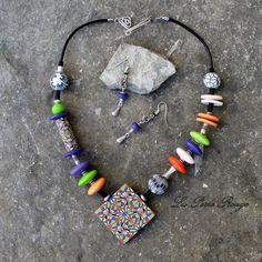 Parure collier asymétrique orange, mauve et vert, perles pâte polymère et argent montées sur cuir noir.