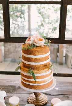 Brides: A Two-Tiered Naked Cake with Fresh Flowers. A two-tiered naked cake topped with pink garden roses and greenery, created by Tiny Boxwoods.