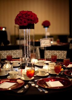 Red rose centerpiece with bling hanging in the glass cylinder! Black chair covers with chair ties. If suggest silver chargers rather than red with red napkins.... Gorgeous!