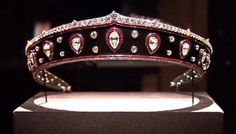 "Cartier, 1914. A blackened steel  kokoshnik-shaped gemset platinum-mounted tiara. The metal band bordered with calibré-cut rubies, with a band of old-mine diamonds above and rose-cut diamonds below, set with thirteen pear-shaped diamonds within calibré-cut ruby-set frames alternating with pairs of collet-set circular-cut diamonds. (photo from the ""Cartier and America"" exhibit of jewels made in America or for Americans.) Provenance: Queen Marie of Romania"