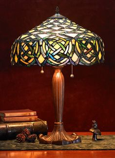 Celtic Knotwork Lamp In the Tiffany style of an age gone by, this elegant lamp features blue and green knotwork glowing against the warm background of its magnificent stained-glass shade. Dual lights operate independently, each with its own pull chain. $248