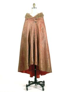 Jeanne Lanvin Tangerine Gold Lame Cape   French, Summer 1931   Decorative topstitching throughout in Art Deco seascape fantasy scene, with beige sheared beaver collar and facings, cape controlled by double seamed yoke lined in beaver, two sterling silver filigree pendant buttons with loops, curved hem higher at front
