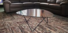 A thick 10mm tempered glass-top coffee table with a steel geometric base