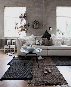 Natuurlijke tinten en materialen, gebreide kussens, aardewerk potten, geweven kleden, betonlook wanden