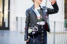 A graphic t-shirt is paired with a patched leather jacket, patched Chanel bag, and button-front denim skirt