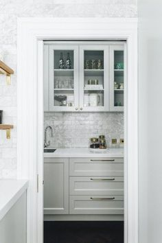 The pretty pantry offers glass front doors for crockery display and the brass hardware, Perrin & Rowe Oberon Mixer and marble splashback assist in elevating the space overall. Pantry Design, Kitchen Design, Newtown House, Glass Front Door, Front Doors, White Bench, Kitchen Taps, Butler Pantry, Splashback