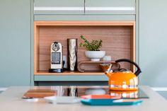 Decoração de apartamento moderno, escandinavo, branco. Plantas nos detalhes da decoração da cozinha e nicho de madeira.