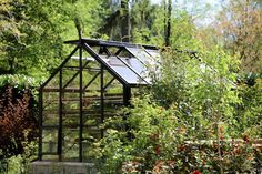 Beautiful 8x12 Cottage greenhouse nestled in the garden. See more examples in our free catalog!