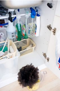 Hang spray bottles on a tension rod under sink - GENIOUS