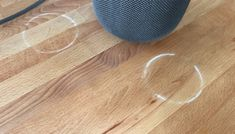 Oils that are diffused between the speaker's silicone base and the wood are the cause of the white rings.