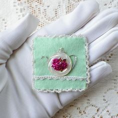 This is a handmade brooch of my own idea and design. It is made of mint green felt on which has been added a piece of vintage lace, glass beads, pink metal rose beads, embroidery thread, and a beautiful round mother of pearl vintage button--positioned and stitched to look like a teapot. There is a simple clasp on the back. The brooch measures approximately 2 x 2.