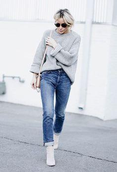 Street style look com sueter cinza, calça jeans, bota bege e óculos de sol.