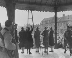 Belgian women who collaborated with the Germans during the occupation are forced to give the Nazi salute before their jeering countrymen. The women's heads were all shaven as part of their public humiliation.