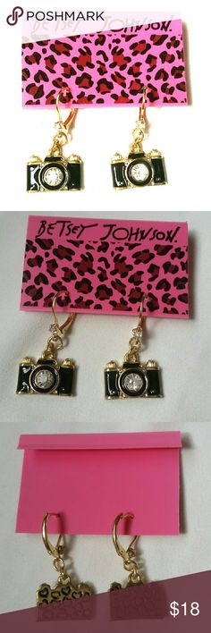 """Betsey Johnson Black Camera Dangle Earrings New with original backing card Betsey Johnson highly polished gold tone metal with black enamel camera earrings, with a super sparkly diamond rhinestone crystal inset for the lens, 4 tiny ones surrounding it, and one at the base of the leverback earring finding. The backs are stamped with Betsey's trademark hearts. They measure 3/4"""" long from the base of the leverback, and 5/8"""" wide.   Thank you for checking out my closet, and happy poshing!! :)…"""