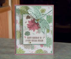 This pretty card measures 5 1/2 x 4 1/4, with all images & wording, in the center panel, being hand stamped. The card was made using Stampin Up stamp sets, card stocks, coordinating designer series paper, dragonfly dies & gold enamel dots. Each of the floral images were stamped with the outline, then stamped with the fill-in colors. Go ahead and fluff the vellum dragonfly wings, they are securely glued in place. Inside: The card is blank, so you can add your own happy wis...