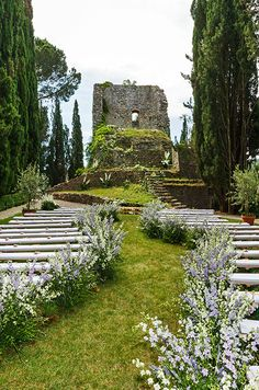 Wedding aisle lined with wild lavender leads to a full orchestra at the far end of the garden.