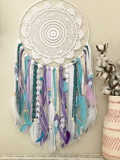 The perfect addition to a girls bedroom or a nursery. This dream catcher is a beautiful combination of purple, turquoise and white ribbons, lace and yarn. Lots of colorful stones, wooden beads and fun feathers give this dream catcher a great personality. It comes with 3 hand painted feathers with boho designs. This boho wall hanging would look great in a purple bedroom or with matching bedding. To customize any details visit www.shopwildcotton.com