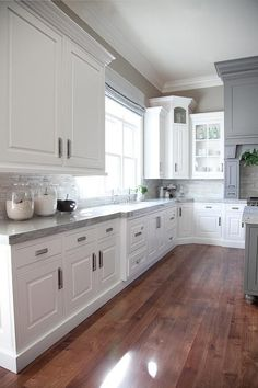 Grey and white kitchen features crisp white cabinets adorned with nickel hardware paired with gray countertops and a linear marble tiled backsplash.