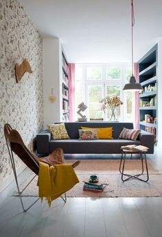 living room with floral wallpaper and pink curtains. not too sweet. balanced by retro sling chair.