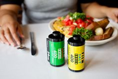 """Check out this clever little salt and pepper set: it's designed to look like 35mm rolls of Kodak and Fujifilm film. The yellow one is the """"Film Salt Shaker,"""" and the green one is the """"Film Pepper Shaker."""""""
