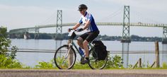cyclist riding on a trail with a lake and a bridge in the background St Lawrence, The Province, The St, Leeds, Quebec, Toronto, Trail, Cycling, Bridge